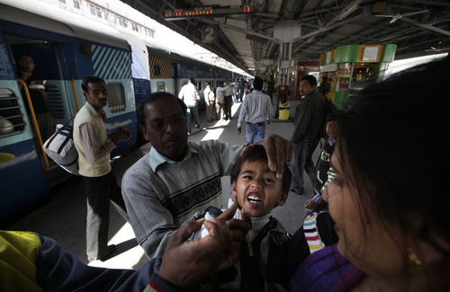A child reacts after being administered polio drops by health workers at a railway station in New Delhi, India, Saturday, Feb. 25, 2012. India officially won its battle with polio as it was removed from the World Health Organization's list of countries plagued by the crippling disease. (AP Photo/Manish Swarup)