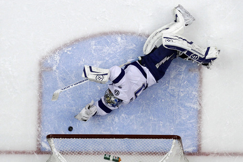 Tampa Bay Lightning goalie Dwayne Roloson (30) can't stop a shot by Pittsburgh Penguins' Jordan Staal in the second period of an NHL hockey game in Pittsburgh Saturday, Feb. 25, 2012. It was Staal's second goal of the game, and the Penguins went on to win 8-1. (AP Photo/Gene J. Puskar)