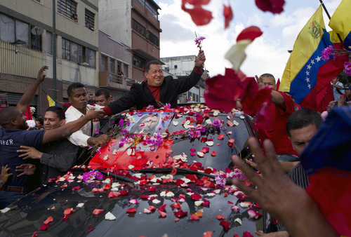 Venezuela's President Hugo Chavez, top, greets supporters during a caravan from Miraflores government palace to Simon Bolivar airport in Caracas, Venezuela, Friday, Feb. 24, 2012. Venezuelan President Hugo Chavez is on his way to Cuba to have a tumor removed from the same region of the pelvis where he had cancer surgery last year. (AP Photo/Ariana Cubillos)