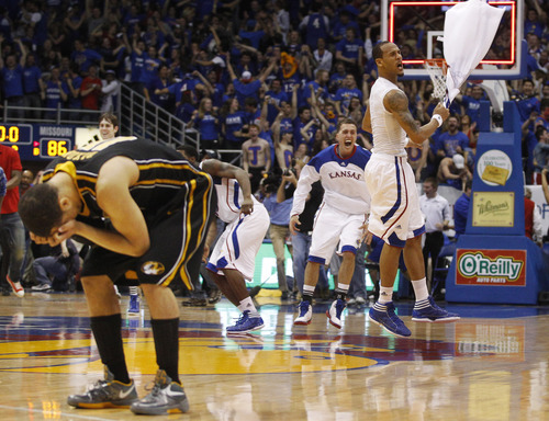 Missouri guard Michael Dixon (11) hold his head while Kansas guard Travis Releford waves a towel in celebration following an NCAA college basketball game in Lawrence, Kan., Saturday, Feb. 25, 2012. Kansas defeated Missouri 87-86 in overtime.(AP Photo/Orlin Wagner)