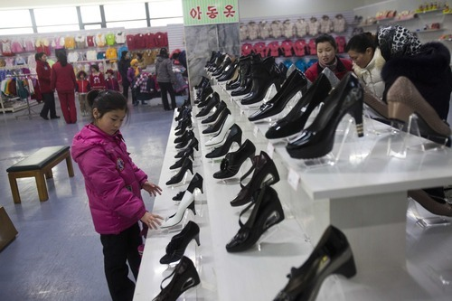 In this Thursday, Jan. 19, 2012 photo, a girl looks at shoes for women at the Kwangbok Area shopping center in Pyongyang, North Korea. A new culture of commerce is springing up, with China as its inspiration and source. The new consumerism is part of a campaign launched three years ago to build up the economy, and so the image of new leader Kim Jong Un. (AP Photo/David Guttenfelder) PART OF A 34 PICTURE SERIES BY DAVID GUTTENFELDER