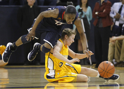 Connecticut's Brianna Banks, left, reaches for a loose ball over Marquette's Gabi Minix, during the second half of an NCAA college basketball game Saturday, Feb. 25, 2012, in Milwaukee. (AP Photo/Jeffrey Phelps)