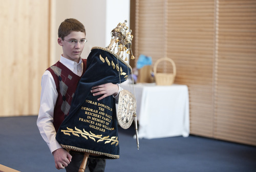 Charlie Barth carries a Torah scroll at Temple Har Shalom in Park City during his bar mitzvah last year. In Judaism, a bar mitzvah signifies entry into Jewish adulthood. Courtesy Deborah DeKoff