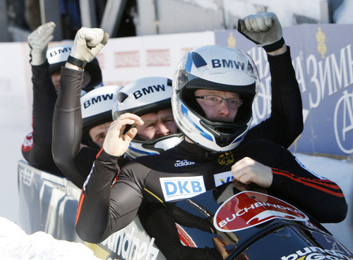 Germany 2 pilot Manuel Machata right, with pushers Marko Huebenbecker, Andreas Bredau and brakeman Christian Poser, react after their third-place finish in the men's four-man Bobsled World Championships in Lake Placid, N.Y., on Sunday, Feb. 26, 2012. (AP Photo/Mike Groll)