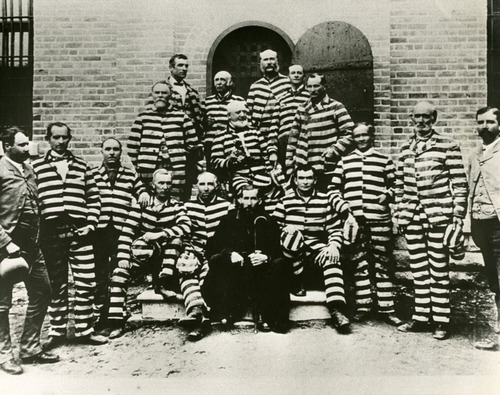 Tribune file photo  Polygamists including: Joseph Stacey Murdock (2nd row far left with white moustache and goatee), James E. Hamilton (behind Murdock), George Q. Cannnon (2nd row center, right of Murdock), Daniel B. Hill (Third row top right), Amundsen (2nd row right of Cannon),  Hans Jesperson (Bottom row third from far right), and Dow (bottom row far right)