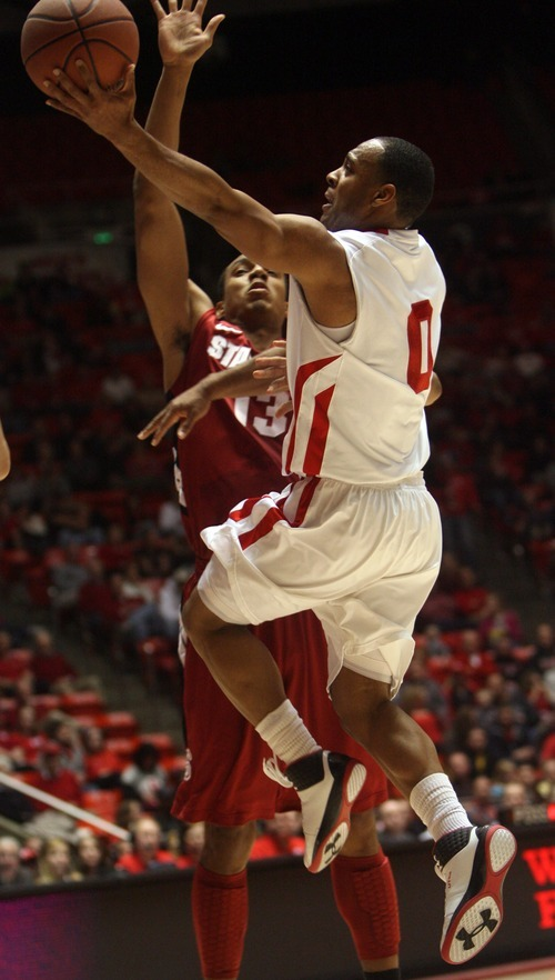 Kim Raff  |  The Salt Lake Tribune University of Utah player Chris Hines attempts a layup as Stanford player Josh Owens defends during the first half at the Huntsman Center in Salt Lake City, Utah on February 25, 2012.