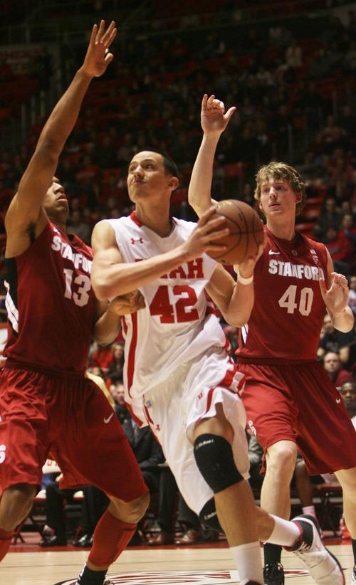 Kim Raff  |  The Salt Lake Tribune University of Utah player Jason Washburn drives the basket past Stanford players (left) Josh Owens and John Gage during a game at the Huntsman Center in Salt Lake City, Utah on February 25, 2012. Utah went on to win 58-57.