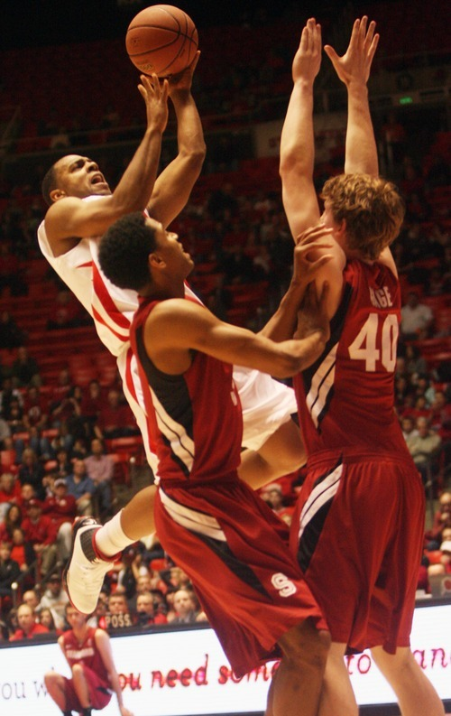 Kim Raff  |  The Salt Lake Tribune University of Utah player Chris Hines takes a shot as Stanford players (left) Anthony Brown and John Gage defend during a game at the Huntsman Center in Salt Lake City, Utah on February 25, 2012. Utah went on to win 58-57.