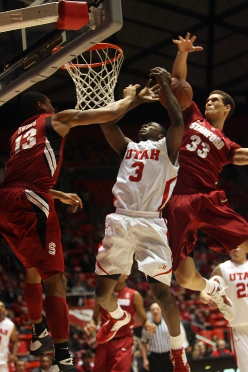 Kim Raff  |  The Salt Lake Tribune University of Utah player Anthony Odunsi is foul while taking a shot as Stanford players (left) Josh Owens and Dwight Powell defend during the first half at the Huntsman Center in Salt Lake City, Utah on February 25, 2012.