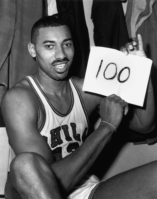 In this March 2, 1962, photo, Wilt Chamberlain of the Philadelphia Warriors holds a sign reading