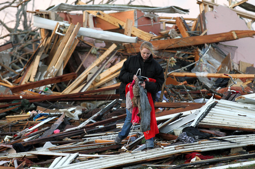 In this photo provided by SWAT Chasers via the Indianapolis Star, a person looks at wreckage in Henryville, Ind., Friday, March 2, 2012, after a series of powerful tornadoes tore through southern Indiana, killing at least 14 people and leaving several small towns in ruin. At least one person was confirmed dead in hard-hit Henryville. (AP Photo/SWAT Chasers, Chris Bergin via the Indianapolis Star)