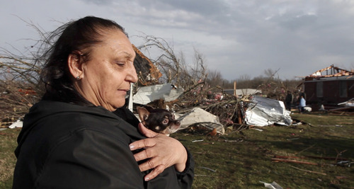 Jeanie Lewellyn and her dog Bell Bell stand outside the remains of their home, which was destroyed by a tornado that ripped through their Pekin, Ind. neighborhood, outside of New Pekin, Ind. Friday, March 2, 2012. Authorities in Indiana say at least ten people have been killed in violent storms that spawned tornadoes across a wide swath of southern Indiana. (AP Photo/The Courier-Journal, Matt Stone)