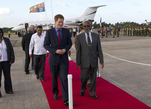 Britain's Prince Harry, centre left, as he arrives at Philip Goldson International Airport, Ladyville, Belize, where he was met by the Governor General of Belize, Sir Colville Young at the start of his tour to mark the Queen's Diamond Jubilee, Friday March 2, 2012.  Prince Harry will spend the next seven days visiting three of his grandmother's realms of Belize, Bahamas and Jamaica, in honour of her 60-year reign.  (AP Photo/Arthur Edwards)