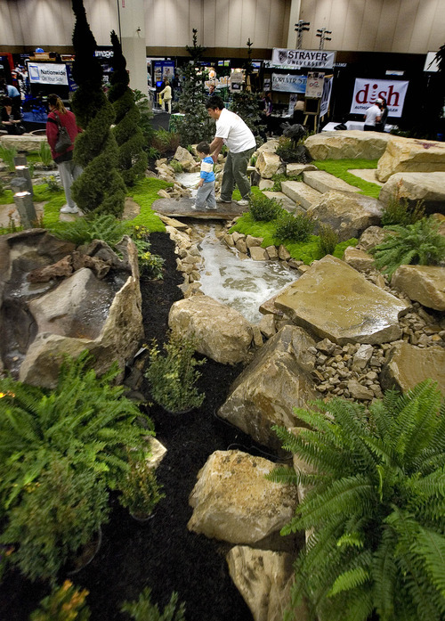 Paul Fraughton | The Salt Lake Tribune. Elwood Longenecker and his son Dax, age 3, walk Thursday through a garden landscape designed by Stonescapes, one of hundreds of companies represented at this year's Salt Lake Tribune Home & Garden Festival that runs through Sunday at the South Towne Expo Center in Sandy.
