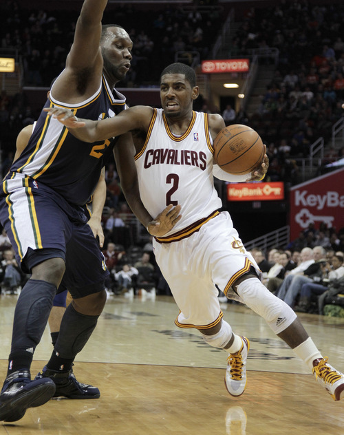 Cleveland Cavaliers' Kyrie Irving (2) drives to the basket against Utah Jazz's Al Jefferson (25) in the second half of an NBA basketball game in Cleveland on Monday, March 5, 2012. (AP Photo/Amy Sancetta)