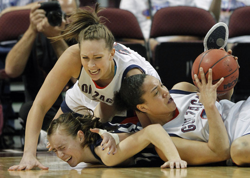 Gonzaga's Haiden Palmer, right, and Shannon Reader, center, battle for a loose ball against BYU's Lexi Eaton in the first half during the NCAA West Coast Conference tournament championship basketball game, Monday, March 5, 2012, in Las Vegas.  (AP Photo/Julie Jacobson)