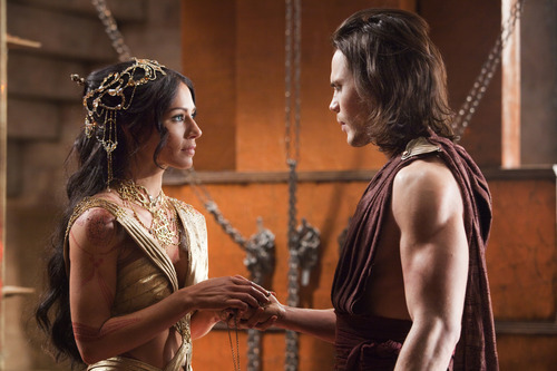 In this film image released by Disney, Lynn Collins portrays Dejah Thoris, left, and Taylor Kitsch portrays John Carter in a scene from