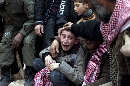 Ahmed, center, mourns his father Abdulaziz Abu Ahmed Khrer, who was killed by a Syrian Army sniper, during his funeral in Idlib, north Syria, Thursday, March 8, 2012. (AP Photo/Rodrigo Abd)