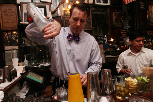 Doug Quinn, left, works at the bar at P.J. Clarke's Thursday, March 8, 2012 in New York. (AP Photo/Tina Fineberg)