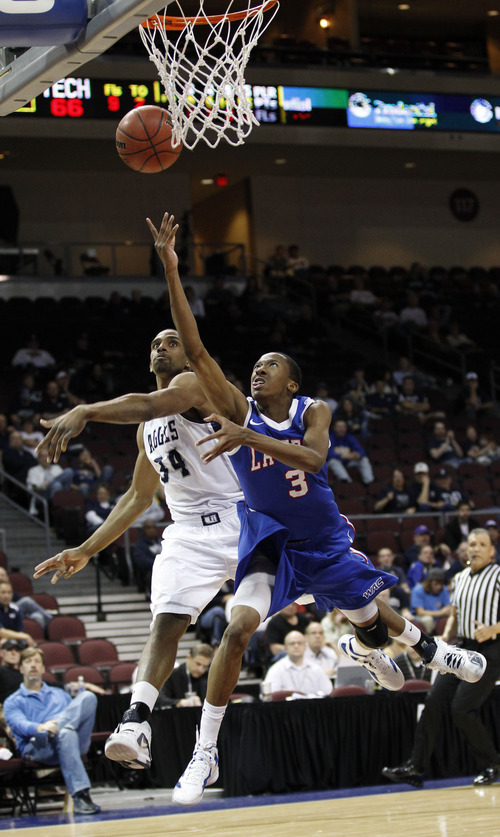 Utah State forward Kyisean Reed (34) fouls Louisiana Tech guard Raheem Appleby (3) for a three point play during their NCAA college basketball game in the Western Athletic Conference tournament Thursday, March 8, 2012, at The Orleans Arena in Las Vegas. Louisiana Tech defeated Utah State 72-70. (AP Photo/Eric Jamison)