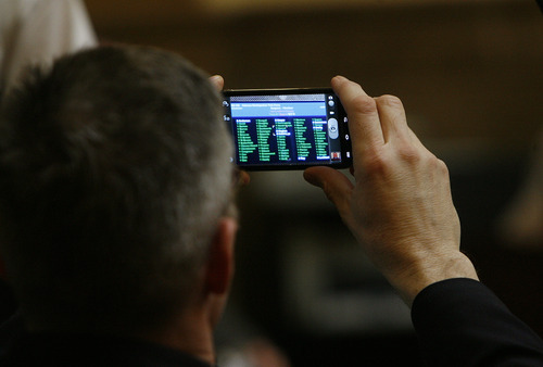 Scott Sommerdorf  |  The Salt Lake Tribune              Rep. Tim Cosgrove, D-Murray, takes a photo of his bill passing through the Utah House of Representatives Thursday. His bill, HB162 - Veterans Reintigration Task Force, passed easily on the final day of the session.