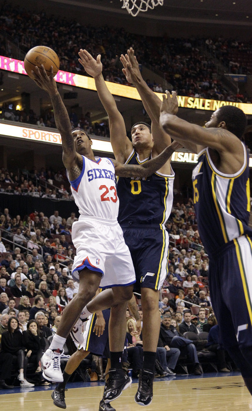 Philadelphia 76ers' Lou Williams (23) goes up for a shot as Utah Jazz's Enes Kanter (0), of Turkey, and Derrick Favors (15) defend in the first half of an NBA basketball game on Friday, March 9, 2012, in Philadelphia. (AP Photo/Matt Slocum)