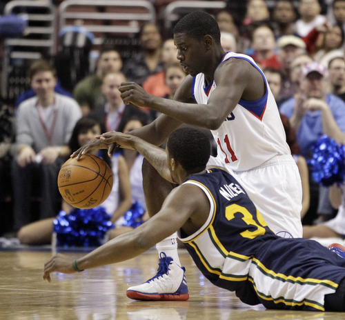 Philadelphia 76ers' Jrue Holiday, top, and Utah Jazz's C.J. Miles battle for a loose ball in the second half of an NBA basketball game on Friday, March 9, 2012, in Philadelphia. Philadelphia won 104-91. (AP Photo/Matt Slocum)