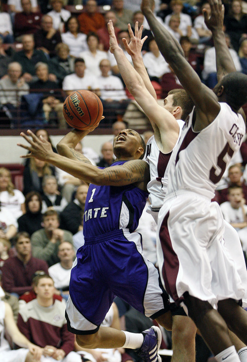 Weber State guard Damian Lillard (1) goes up under the basket in front of Montana guard Will Cherry (5) and forward Mike Weisner, center,  during the first half of an NCAA college basketball game in Missoula, Mont., on Tuesday, Feb. 28, 2012. (AP Photo/Michael Albans)