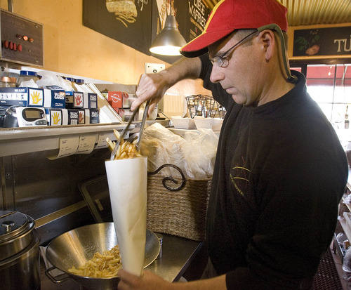 Paul Fraughton | The Salt Lake Tribune Pierre Vandamme, of Bruges Waffles and Frites, readies  an order of Belgian frites (fries).