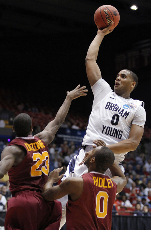 Brigham Young forward Brandon Davies (0) shoots against Iona forward Randy Dezouvre (23) and forward Taaj Ridley in the first half of an NCAA men's college basketball tournament opening-round game Tuesday, March 13, 2012, in Dayton, Ohio. (AP Photo/Skip Peterson)