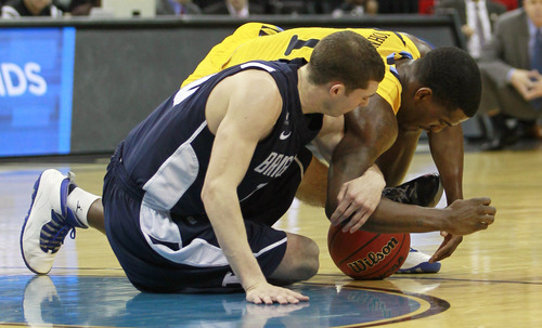 BYU guard Matt Carlino (10) fights Marquette guard Darius Johnson-Odom (1) for a loose ball in the second half of their NCAA tournament second-round college basketball game in Louisville, Ky., Thursday, March 15, 2012. Marquette beat BYU 88-68. (AP Photo/John Bazemore)
