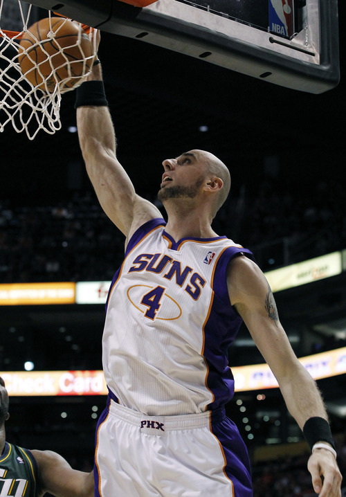 Phoenix Suns' Marcin Gortat (4), of Poland, dunks against the Utah Jazz in the second quarter of an NBA basketball game Wednesday, March 14, 2012, in Phoenix. (AP Photo/Ross D. Franklin)