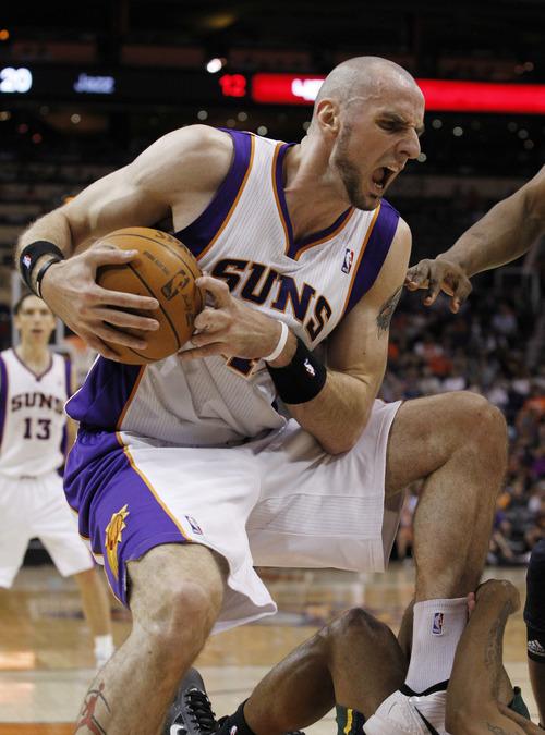 Phoenix Suns' Marcin Gortat, of Poland, falls on Utah Jazz's Earl Watson in the first quarter of an NBA basketball game Wednesday, March 14, 2012, in Phoenix.(AP Photo/Ross D. Franklin)