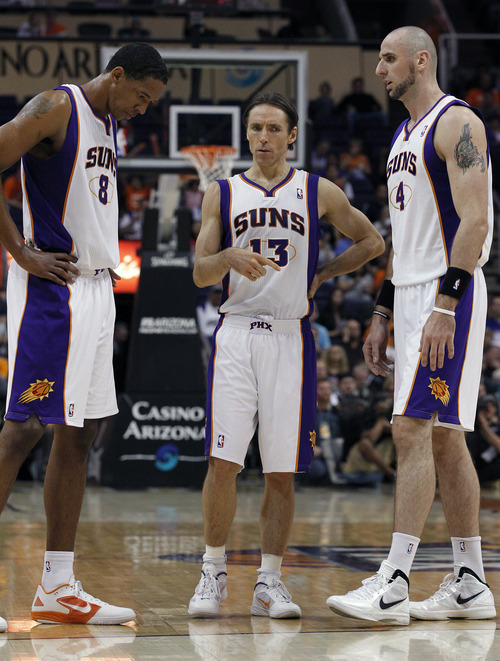 Phoenix Suns' Steve Nash (13) talks with teammates Channing Frye (8) and Marcin Gortat (4), of Poland, during a break in the action in the second quarter of an NBA basketball game against the Utah Jazz Wednesday, March 14, 2012, in Phoenix. (AP Photo/Ross D. Franklin)