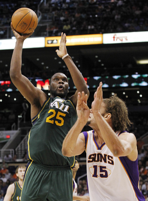 Utah Jazz's Al Jefferson (25) shoots over Phoenix Suns' Robin Lopez (15) in the fourth quarter of an NBA basketball game Wednesday, March 14, 2012, in Phoenix.  The Suns defeated the Jazz 120-111.(AP Photo/Ross D. Franklin)
