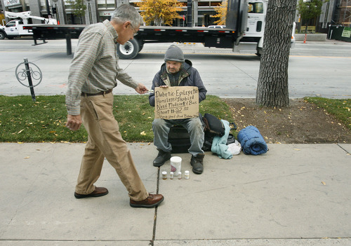 SCOTT SOMMERDORF  |  Tribune file photo Phil Pugsley, left, stops to give 57-year-old George Donald some money as Donald sits on the sidewalk on South Temple. Orem City Council on Tuesday, Jan. 10, 2012, considers ordinances that would prohibit aggressive panhandling.