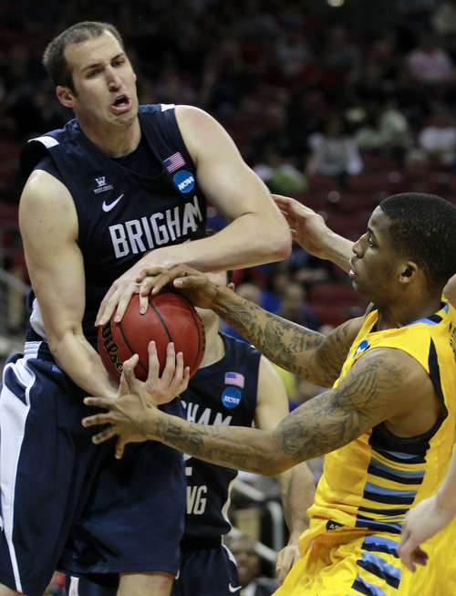 BYU forward Noah Hartsock (34) battles Marquette guard Vander Blue (2) for a rebound in the second half of their NCAA tournament second-round college basketball game in Louisville, Ky., Thursday, March 15, 2012. Marquette beat BYU 88-68. (AP Photo/John Bazemore)