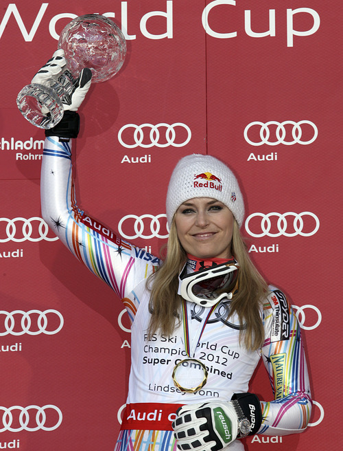 Lindsey Vonn, of the United States, shows her trophy for winning the alpine ski, women's World Cup super-combined discipline title in Schladming, Austria, Saturday, March 17, 2012. (AP Photo/Armando Trovati)