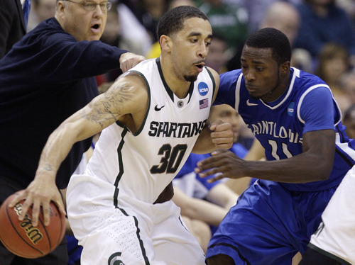 Michigan State's Brandon Wood, left, looks for an open pass as Saint Louis' Mike McCall Jr. defends during the first half of an NCAA college basketball tournament third-round game Sunday, March 18, 2012, in Columbus, Ohio. (AP Photo/Jay LaPrete)