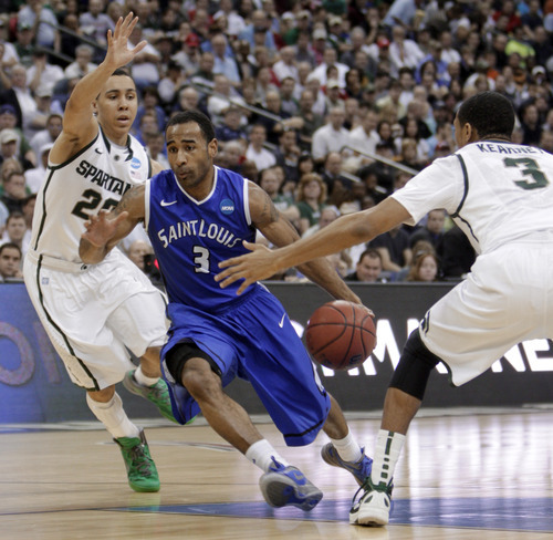 Saint Louis' Kwamain Mitchell (3) drives between Michigan State's Travis Trice (20) and Brandan Kearney (3) during the first half of an NCAA men's college basketball tournament third-round game in Columbus, Ohio, Sunday, March 18, 2012. (AP Photo/Jay LaPrete)