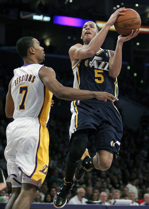 Utah Jazz guard Devin Harris (5) goes up against Los Angeles Lakers guard Ramon Sessions (7) during the first half of an NBA basketball game in Los Angeles, Sunday, March 18, 2012. (AP Photo/Alex Gallardo)