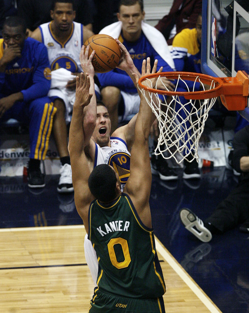 Scott Sommerdorf  |  The Salt Lake Tribune              Jazz center Enes Kanter blocks Golden State's forward David Lee's path to the hoops during first half play. The Utah Jazz trailed the Golden State Warriors 51-46 at the half at Energy Solutions Arena, Saturday, March 17, 2012.