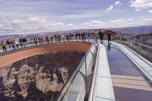 FILE - In this March 28, 2007 file photo, tourists walk on the glass-bottomed Skywalk that extends 70 feet over the edge of Grand Canyon West's Eagle Point, in Arizona. A Las Vegas developer must keep fighting in tribal court as he tries to retain his contractual rights to the Grand Canyon Skywalk, a federal judge ruled Monday, March 19, 2012.  (AP Photo/The Arizona Republic, Rob Schumacher, File) MARICOPA COUNTY OUT; MAGS OUT; NO SALES