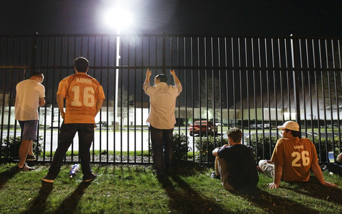 Fans wait outside the Tennessee Titans NFL football team offices for a glimpse of former Indianapolis Colts quarterback Peyton Manning while Manning meets with team officials inside on Wednesday, March 14, 2012, in Nashville, Tenn. (AP Photo/Mark Humphrey)