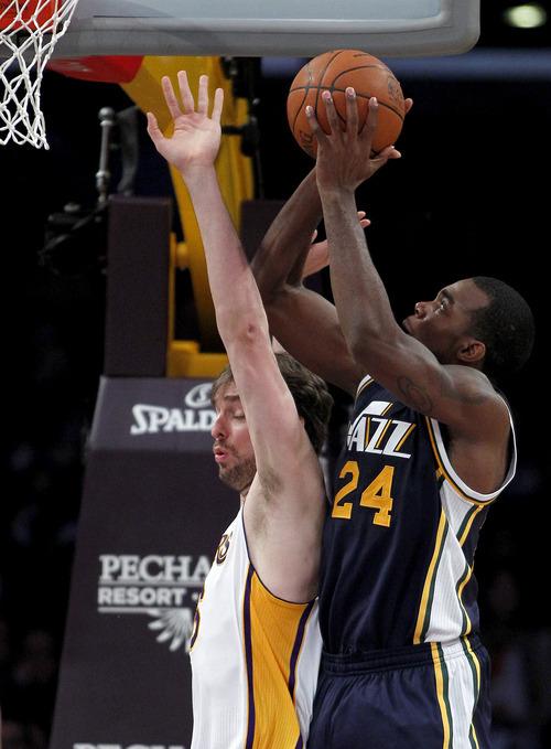 Utah Jazz forward Paul Millsap (24) shoots over Los Angeles Lakers forward Pau Gasol, left, of Spain, during the first half of an NBA basketball game in Los Angeles, Sunday, March 18, 2012. (AP Photo/Alex Gallardo)