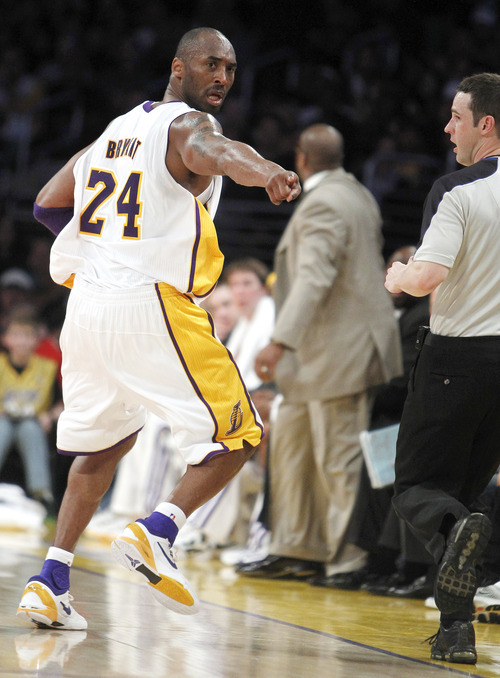 Los Angeles Lakers guard Kobe Bryant (24) points out a spot to referee Mark Wunderlich, right, after a call goes to the Utah Jazz during the first half of an NBA basketball game in Los Angeles, Sunday, March 18, 2012. (AP Photo/Alex Gallardo)