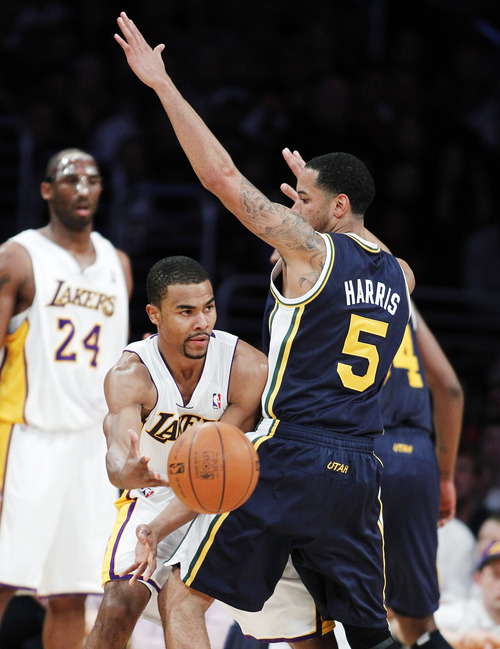 Los Angeles Lakers guard Ramon Sessions (7) passes the ball around Utah Jazz guard Devin Harris (5) during the first half of an NBA basketball game in Los Angeles, Sunday, March 18, 2012. (AP Photo/Alex Gallardo)
