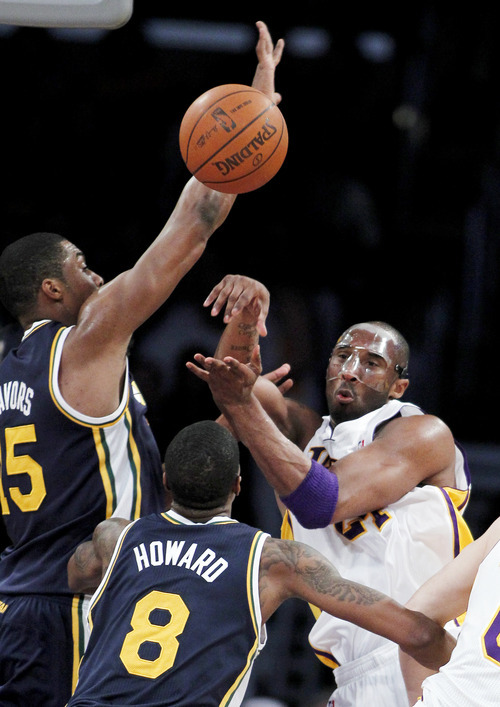 Los Angeles Lakers guard Kobe Bryant (24) passes the ball with Utah Jazz forwards Derrick Favors (15) and Josh Howard (8) defending during the first half of an NBA basketball game in Los Angeles, Sunday, March 18, 2012. (AP Photo/Alex Gallardo)