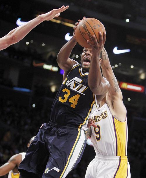 Utah Jazz small forward C.J. Miles (34) shoots against Los Angeles Lakers forward Matt Barnes (9) during the first half of an NBA basketball game in Los Angeles, Sunday, March 18, 2012. (AP Photo/Alex Gallardo)