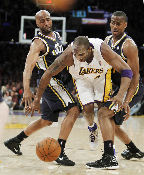 Los Angeles Lakers guard Kobe Bryant, center, splits between Utah Jazz guards Jamaal Tinsley, left, and Alec Burks during the first half of an NBA basketball game in Los Angeles, Sunday, March 18, 2012. (AP Photo/Alex Gallardo)